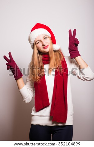 Christmas girl shows a gesture of peace, two fingers. Santa hat isolated portrait of a woman on a gray background. - stock photo