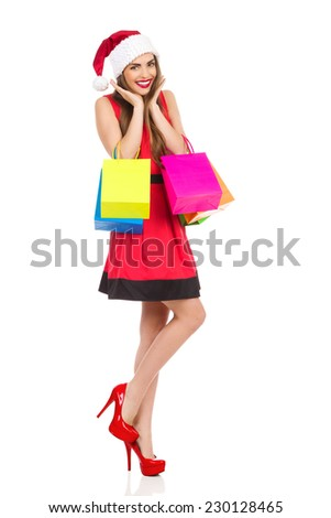 Christmas girl standing on one leg and holding colorful shopping bags. Full length studio shot isolated on white. - stock photo