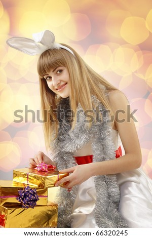 christmas girl teenager with rabbit ears open gifts over golden light  background