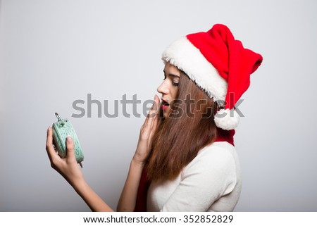 Christmas girl with alarm clock yawning. Santa hat isolated portrait of a woman on a gray background. - stock photo