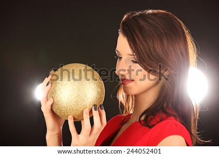 Christmas girl with cristal golden ball in her hand, studio - stock photo
