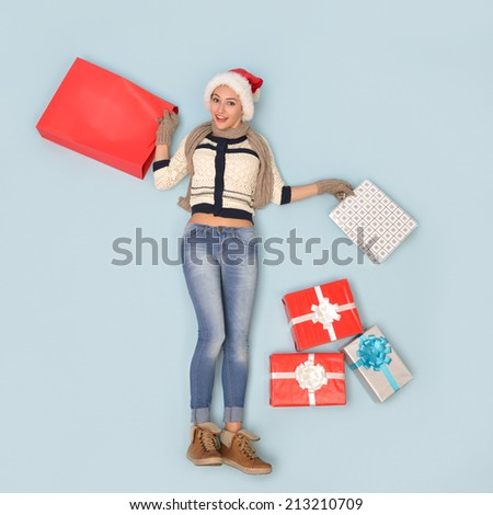Christmas girl with gift and shopping bags in santa's hat over blue background - stock photo