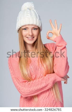 Christmas girl, young beautiful smiling woman giving OK sign over grey background - stock photo