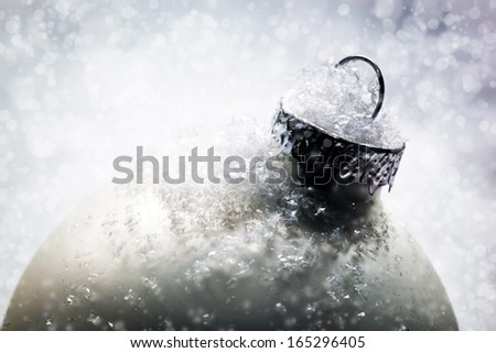 Christmas glass ball on snow, winter background, frost, glittering lights.