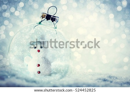 Christmas glass ball with snowman inside. Snowy, glitter background.
