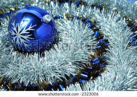 Christmas glass sphere with a pattern on a background of a brilliant celebratory tinsel of two colors