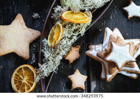 Christmas glazed star shapes cookies with Christmas tree, moss and dry sliced orange in ceramic plate over red wooden table. Dark rustic style, day light. Top view - stock photo