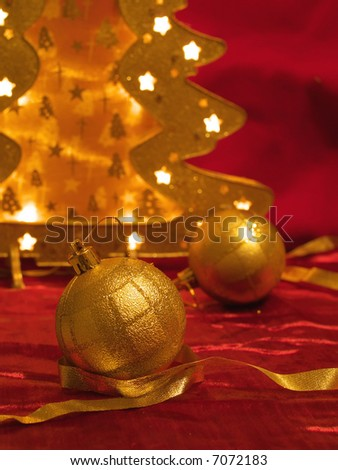 Christmas gold ornaments and gold with lamp like fir on the red background - stock photo