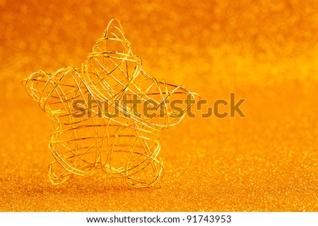 christmas gold wire star on golden glitter background