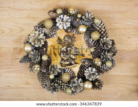 Christmas golden angel with wreath of cones and gold balls on background. - stock photo