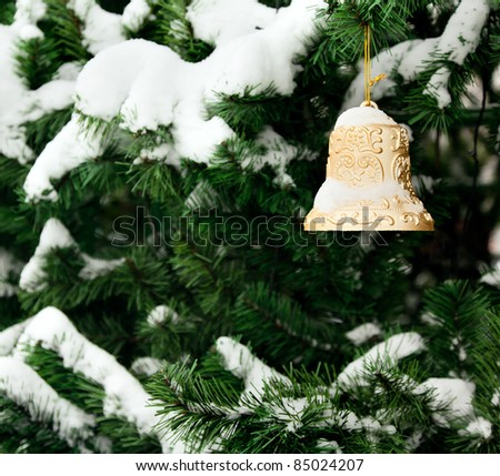 Christmas golden bell on the Christmas tree with snow - stock photo