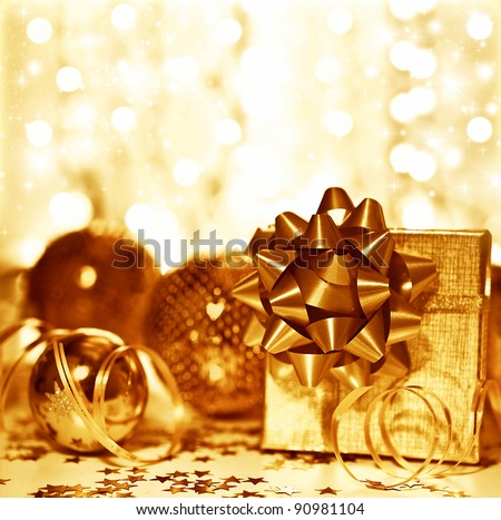 Christmas golden gift decorations, tree ball bauble ornament with present box over blur glowing bokeh lights background, home decor at winter holidays, new year eve - stock photo