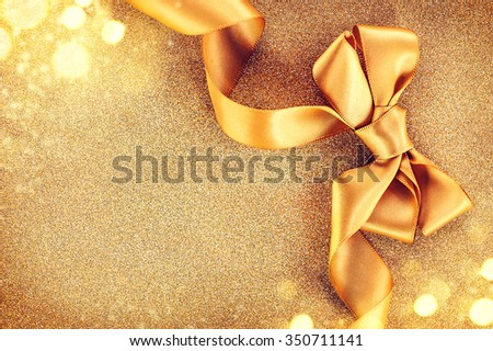 Christmas Golden Satin Ribbon Bow on a Blinking Holiday Background. Greeting Card with copy space for your text. Beautiful Gold Christmas Gift Border art design - stock photo