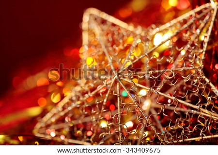 Christmas golden star close-up with blurred lights on red background  - stock photo