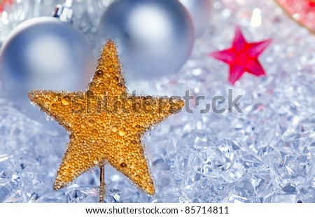 christmas golden star symbol with silver baubles and red ribbon on ice