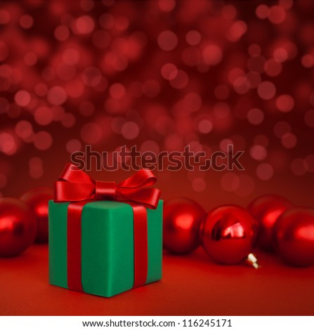 Christmas green gift with red balls on red abstract light background
