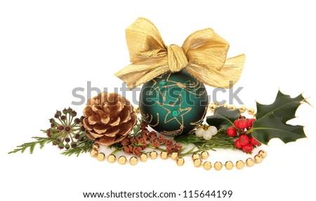 Christmas green sparkling bauble with bow surrounded by holly, mistletoe, ivy and cedar leaf sprigs with gold pine cones and bead chain over white background. - stock photo