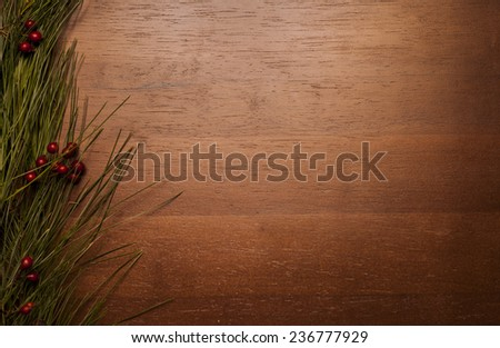 Christmas greenery and red berries on wood background - left side - stock photo