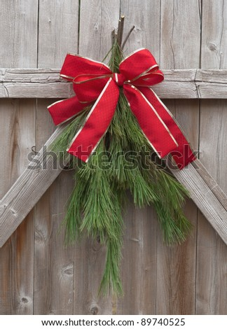Christmas greens tied with red ribbon on a rustic wood fence. - stock photo