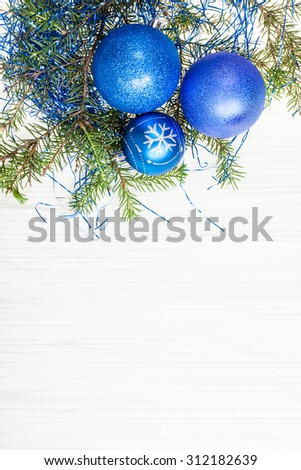 Christmas greeting card - border from three blue Xmas baubles and tree branch on blank paper background