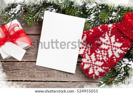 Christmas greeting card, fir tree, mittens and gift box on wooden table. Top view with copy space