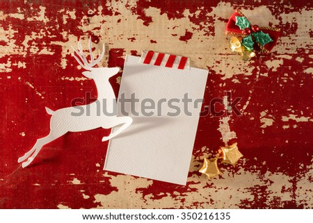 Christmas greeting card top view template mockup, reindeer silhouette with empty paper note and decoration on vintage wood background. Includes clipping path.