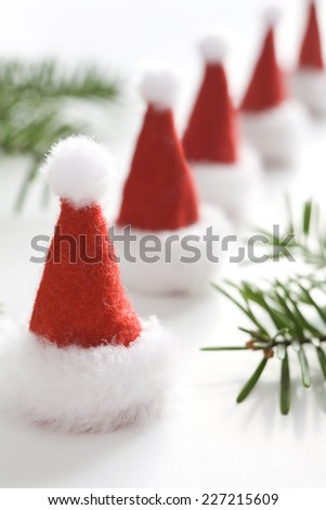 Christmas greeting card with small santa hats. One big santa hat in background. - stock photo