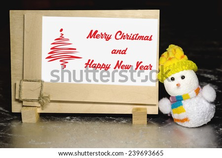 Christmas greeting card with snowman toy and greeting blank wooden frame on silver or metal grunge surface - stock photo