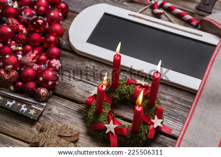 Christmas greeting card with wooden with sign and red decoration. - stock photo