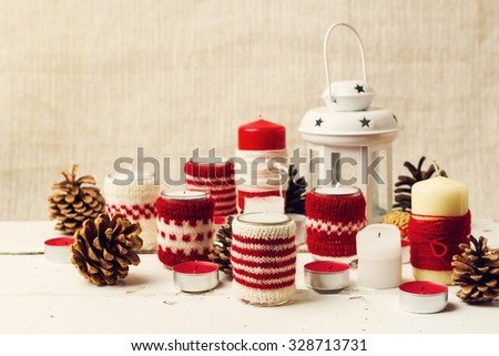 Christmas handmade. Christmas candles in the candle holders knitted. Selective focus. - stock photo