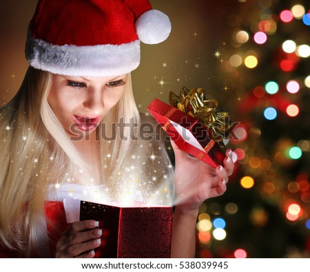 Christmas. Happy Blonde Girl with Santa Hat Opening Gift Box over lights of Christmas tree. Miracle