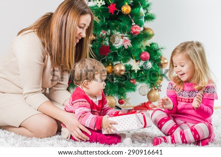 Christmas Happy Family mother and her two little daughters sitting on the floor and open Holidays Gift. - stock photo