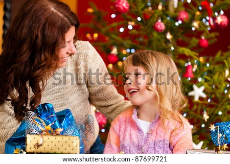 Christmas - happy family (mother with daughter) with gifts on Xmas Eve - stock photo