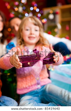 Christmas - happy family (parents with daughter) with gifts on Xmas Eve; focus on gift in front - stock photo
