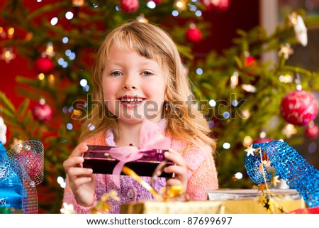 Christmas - happy little girl with Xmas present on Christmas Eve - stock photo