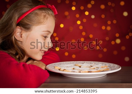 Christmas - happy smiling six years old blond caucasian child girl looking at cookies plate on dark red background with lights - stock photo