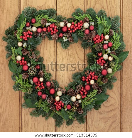 Christmas heart shaped wreath with red bauble decorations, holly, mistletoe and greenery over oak  front door background.
