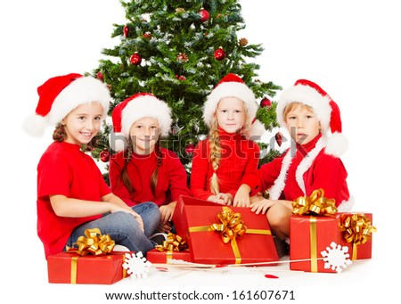 Christmas helpers kids in Santa hat with presents gift box sitting under fir tree. Children over white background.
