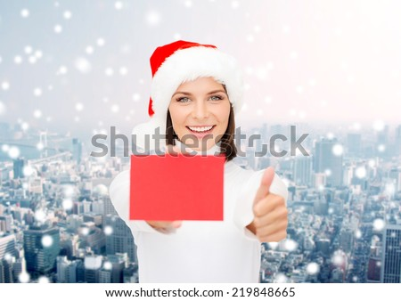christmas, holdays, people, advertisement and sale concept - happy woman in santa helper hat with blank red card showing thumbs up gesture over snowy city background - stock photo