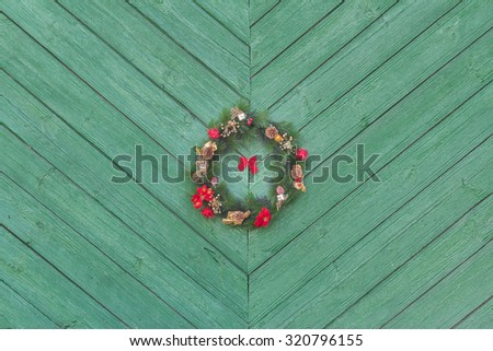 Christmas Holiday Advent wreath hanging outside at green wooden door textured background - stock photo