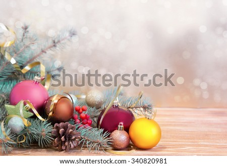 Christmas holiday background. Fir & balls on wood with blurred sparkling background.New Year card  empty space. - stock photo