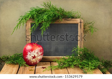Christmas holiday background with chalkboard, apple and pine tree branches - stock photo