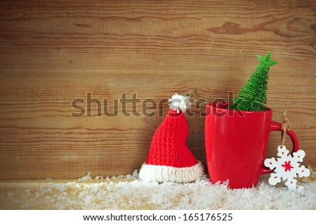 Christmas holiday background with cup of tea, ornaments and fir tree - stock photo