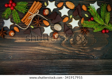 Christmas holiday background with gingerbread cookies, spices and fir branches on the old wooden board. Copy space. Toned - stock photo