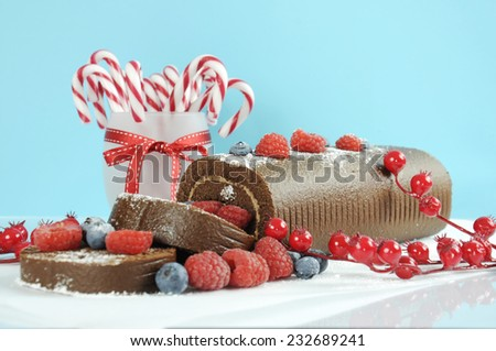 Christmas holiday chocolate roulade yule log swiss roll with berries dessert party food in modern red and white trend against a pale blue and white background. - stock photo