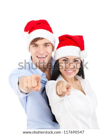 christmas holiday couple  point finger at you looking at camera love smiling embracing in red new year hat cap, man and woman smile, isolated over white background