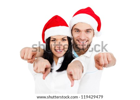 christmas holiday couple point finger at you looking at camera love smiling embracing in red new year hat cap, man and woman smile, isolated over white background - stock photo