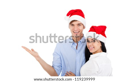 christmas holiday couple point open palm to empty copy space, embracing wear red new year hat cap , man and woman smile looking side, isolated over white background - stock photo