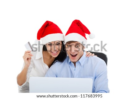 christmas holiday couple shopping on line laptop computer, wear red new year hat cap, excited man and woman hold credit card happy smile, isolated over white background - stock photo