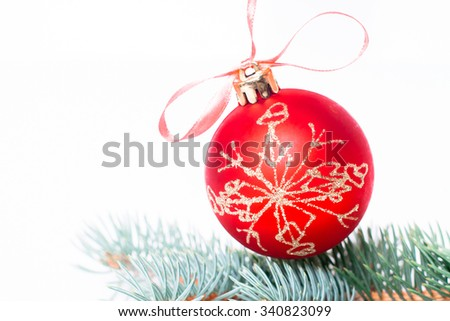 Christmas holiday decoration. Red ornament bauble with branch of fir, pine on white background. Festive merry xmas, new year celebration. Golden shiny light decorative closeup ball.